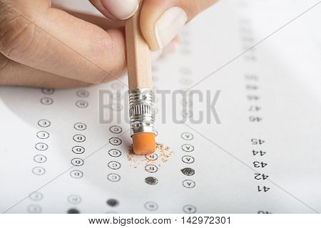 Student erasing test with pencil with eraser tip close up.