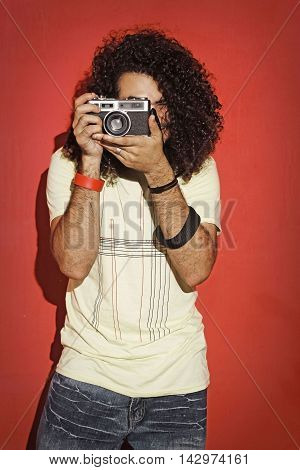 Closeup of one handsome passionate expressive cool young brunette photographer men with long curly hair holding a vintage SLR camera standing against red background