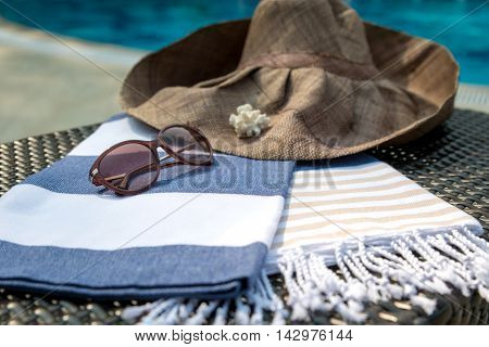 Concept of summer accessories close-up of white, blue and beige Turkish towel, sunglasses and straw hat on rattan lounger with blue swimming pool as background.