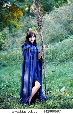 beautiful young witch with a broom in the forest