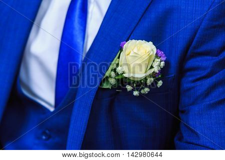 Very beautiful buttonholes on the jacket of a young and handsome groom