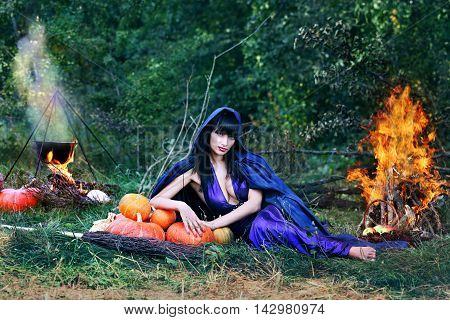 sexy witch near a fire in the forest