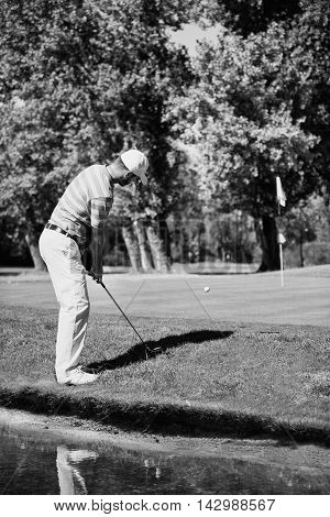 Male golfing next to water hazard, black and white image