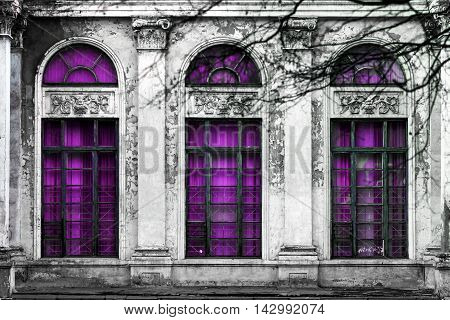 Facade of old abandoned building with three large arched windows of purple glass. Monochrome background