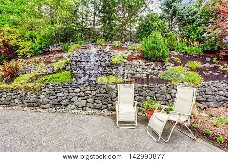 Well Kept Garden With Rocks Desing. Concrete Floor Patio Area With Two Chairs.