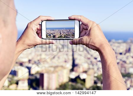 closeup of a young caucasian man taking a picture of Barcelona, Spain, from above with his smartphone