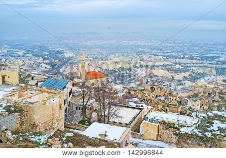 The view from the Uchisar Castle on the town roofs on the hill in foggy winter day Cappadocia Turkey.