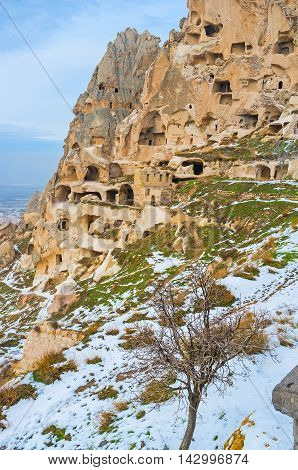 The of the ancient rock with the numerous chambers carved in it that are the parts of the Citadel occupying this rock Uchisar Cappadocia Turkey.