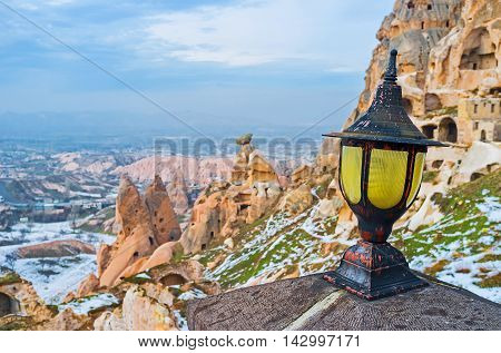 The old style lantern with the ruins of housing of Byzantine period on the background Uchisar Cappadocia Turkey.