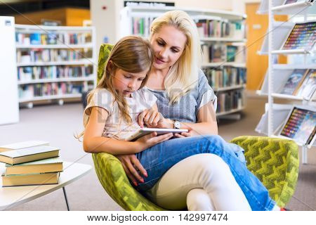 Mother With Daughter Look At Their Touchpad Tablet Device Together In Library