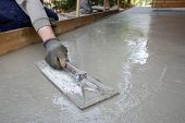 Mason leveling and screeding concrete floor base with square trowel in front of the house. Construction business do-it-yourself precision work around the house concept. poster