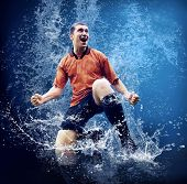 Water drops around football player under water on blue background poster