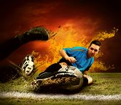 Football player in fires flame on the outdoors field poster