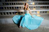 A beautiful blond teen girl sits in front of glass block admiring her prom dress which is spread out around her. She looks like a princess. poster