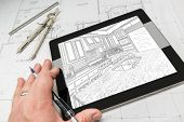 Hand of Architect on Computer Tablet Showing Custom Kitchen Illustration Over House Plans, Compass and Ruler. poster