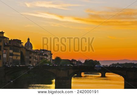 An Evening Stroll: Sunset Over A River In Florence, Italy