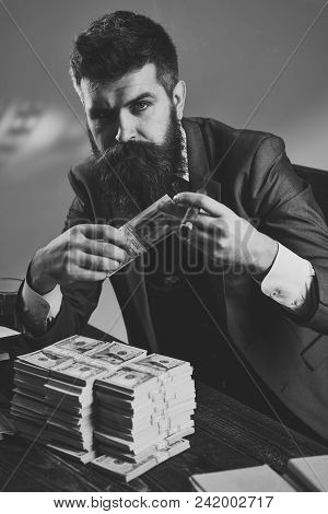Men Face Skin Care. Portrait Men Face In Your Advertisnent. Man Sitting At Table With Piles Of Money