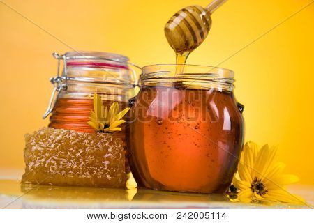 Honey jar, flower with dipper and flowing honey