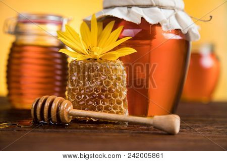 Sweet honey in the comb, glass jar on wooden background