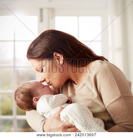 Loving Mother Kissing And Cuddling Newborn Baby At Home poster