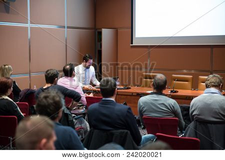 Speaker Giving Talk At Business Meeting. Audience In Conference Room. Coach Answers Questions Of Par