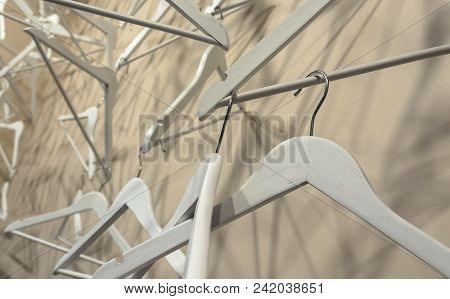 Empty Wooden Clothes Hangers Casting Deep Shadows. Real Coat Hanger Wood Pattern. Abstract Fashion C