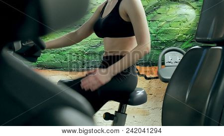 Young Attractive Woman Enhancing Her Endurance While Working Out On An Exercycle. Portrait Of A Beau