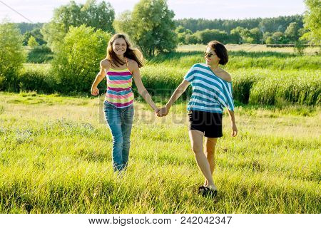 Parent And Teenager, Happy Mother And Teen Daughter 13, 14 Years Old Hold Hands Go Laugh Talk. Backg