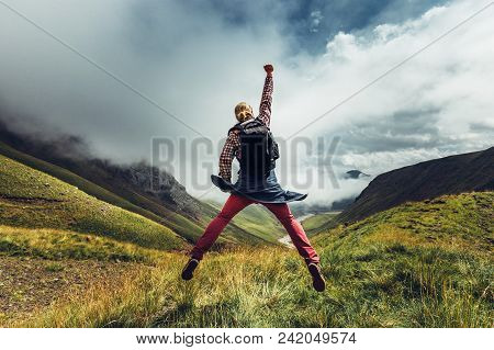 Young Man Traveler Jumps On A Background Of Mountain And Enjoys View Of Summer Mountains. Concept Of