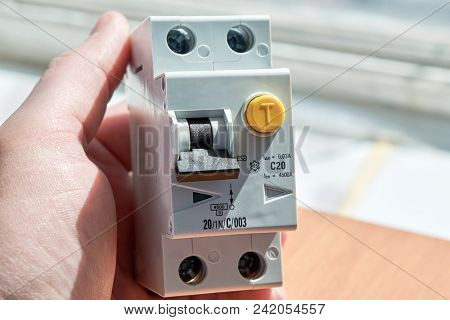 Man Holding An Automatic Switch Of Differential Current. The Device Protects Human Life From Electri