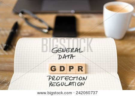 Closeup On Notebook Over Wood Table Background, Focus On Wooden Blocks With Letters Making Gdpr Gene