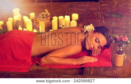 Massage of woman in spa salon. Girl on candles background in therapy room. Luxary interior in oriental therapy salon. Female have relax after sport. Left sun flare of morning light.