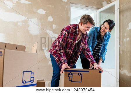 Young couple in love opening cardboard boxes during the renovation of their new home after moving in together