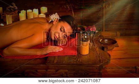 Massage of woman in spa salon. Girl on candles background in therapy room. Luxary interior in oriental therapy salon. Sun rays flare for female have relax after sport. Morning light from right.