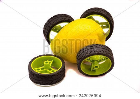 Yellow Lemon Car With Green And Black Wheels With Single, Broken Wheel That Fell Off Isolated On Whi