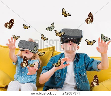Excited Siblings Using Virtual Reality Headset And Looking At Butterflies