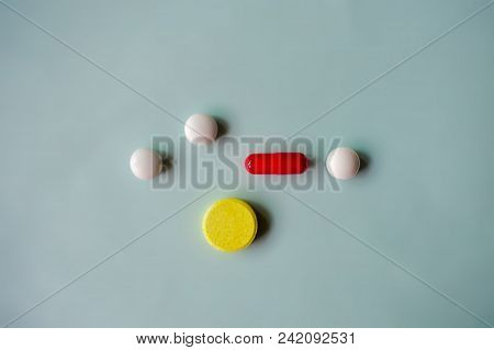 Three White Pills, One Yellow Pill And Red Pill Are On The Light Blue Background