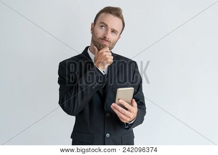 Pensive Business Man Touching Chin, Thinking And Holding Smartphone. Contemplation Concept. Isolated