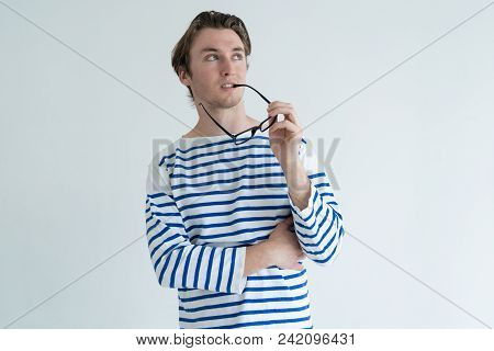 Pensive Young Man Biting Glasses Temple And Thinking. Contemplation Concept. Isolated Front View On
