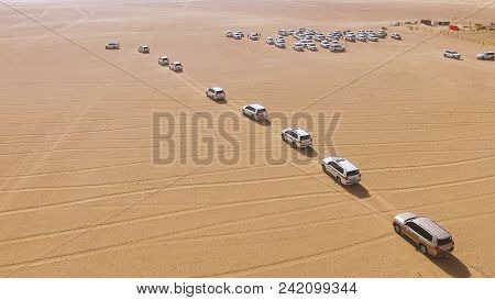 4x4 Suvs Cars Driving Through The Sand Dunes In The Desert Of Abu Dhabi. Stock. Top View On Suvs In