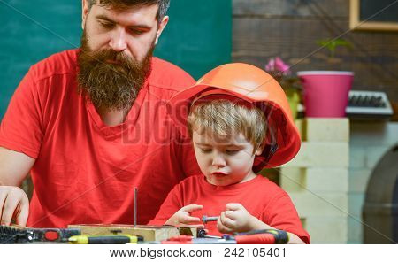 Masculine duties concept. Boy, child busy in protective helmet learning to hammering hobnails with dad. Father, parent with beard teaching little son to use hobnails and hammer. poster