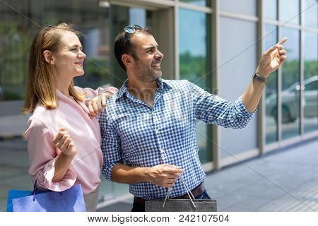 Happy Mid Adult Man With Shopping Bag Pointing Direction To Wife. Caucasian Couple Standing Doing Sh