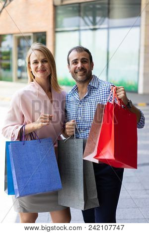 Portrait Of Smiling Husband And Wife Holding Shopping Bags Outdoors. Mid Adult Caucasian Couple Dres
