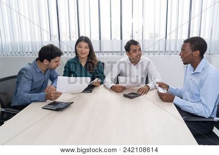 Four Multiethnic Partners Negotiating And Analyzing Financial Reports In Meeting Room. Young Experts