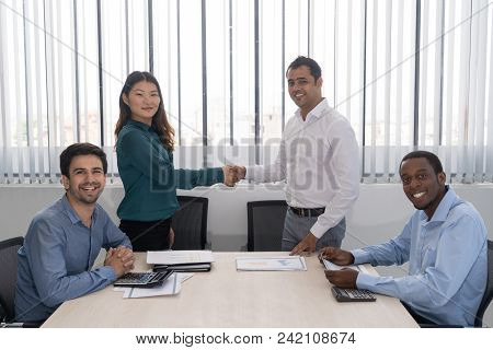 Happy Indian And Chinese Partners Shaking Hands At Business Meeting. Four Mix Raced Business Leaders