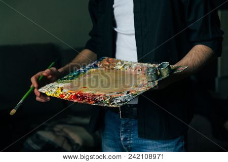 The Artist Holds A Palette With Paints And A Brush. A Man In Jeans And A Black Shirt. Hobby