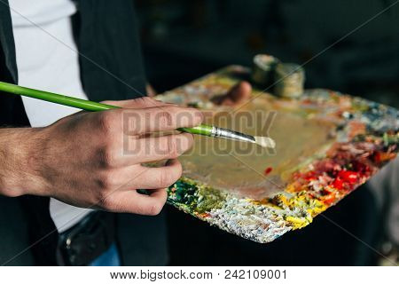 The Artist Holds A Palette With Paints And A Brush And Is Going To Paint On Canvas. A Man In Jeans A