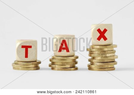 The Word Tax Written With Wood Blocks On Top Of Coins Piles - Tax Increase Concept