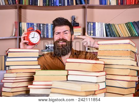 Man, Scientist Peeking Out Of Piles Of Books With Alarm Clock. Teacher Or Student With Beard Studyin