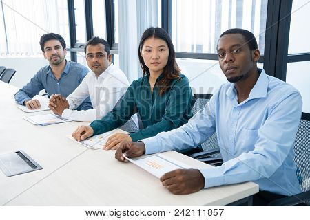 Serious Confident Business Colleagues Analyzing Papers In Board Room. Multiethnic Business People At